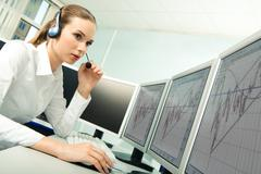 Photo of serious customer service representative sitting before computer while c Stock Photos