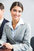 Portrait of successful business lady in suit looking at camera during briefing Stock Photos