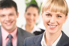 Close-up of blonde woman looking at camera with her business partners behind Stock Photos