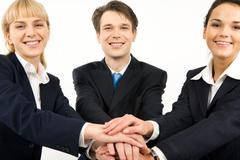Portrait of smiling business partners with a pile of their hands Stock Photos