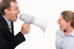 businessman shouting by megaphone opposite screaming woman - stock photo