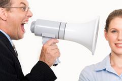 Portrait of businessman holding megaphone shouting straight into woman's ear Stock Photos