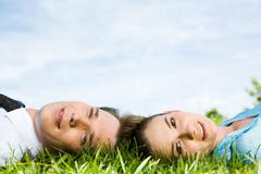 Portrait of pretty woman and businessman lying on the grass Stock Photos