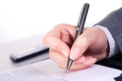 Photo of grey pen in hand over document at workplace Stock Photos