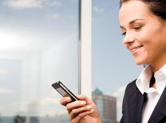 image of pretty woman holding her mobile and sending sms - stock photo