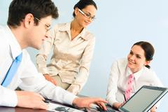Business-team of three smiling people discussing new working ideas Stock Photos