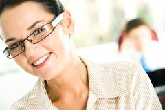 Portrait of happy female in glasses looking at camera with her head slightly asi Stock Photos
