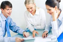 Photo of business partners looking at document and discussing it at meeting Stock Photos