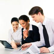 Portrait of business team sitting around table and looking at document while con Stock Photos