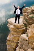 Portrait of happy businessman screaming and standing on the mountain Stock Photos