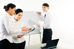 Image of females reading business plan while successful man looking at them read Stock Photos