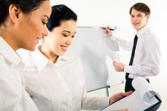 Close-up of business ladies planning their work with happy man near whiteboard a Stock Photos