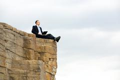 Image of modern businessman on the rocks working on laptop on the background of Stock Photos