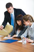Portrait of businesswoman writing on the document with two colleagues near by Stock Photos