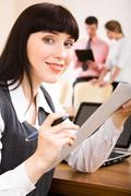 Portrait of confident woman sitting in the office with paper in hand on the back Stock Photos