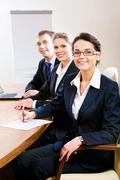 Row of confident white collar workers sitting at the table Stock Photos