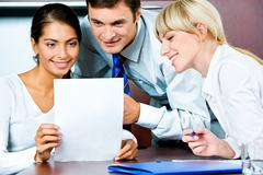 Image of confident business persons looking at the document Stock Photos