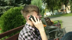 smiling man talking on the phone in park - stock footage