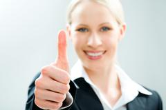 Image of business woman giving the thumbs-up sign Stock Photos