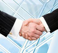 handshake of businesspeople on the background the modern window - stock photo