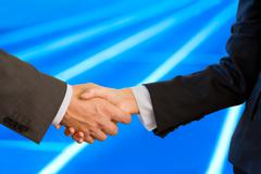 Close-up of two business partners' handshake after making a deal on blue radial Stock Photos
