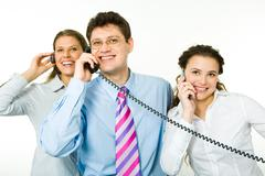 Group of smiling consultants speaking on their phones on white background with m Stock Photos