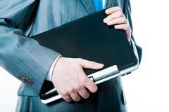 Close-up of  businessman's hands holding black laptop Stock Photos