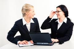 photo of happy women in suits looking at each other with smiles while talking ab - stock photo
