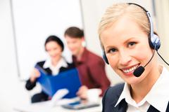 Portrait of customer service representative wearing headset and looking at camer Stock Photos