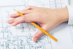 View of human hand with pencil while working at business project Stock Photos