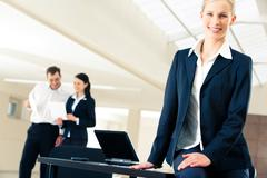 Portrait of elegant business lady at her workplace on the background of working Stock Photos