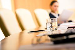 Close-up of glass of water on the background of chairs, papers and working woman Stock Photos