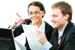 Business woman and man looking at the document and discussing Stock Photos