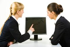Portrait of two businesswomen sitting near computer while one of them pointing a Stock Photos