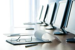 Workplace with open notepad, pen, eyeglasses and monitors on it Stock Photos