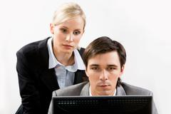 Portrait of two colleagues looking attentively at monitor over white background Stock Photos