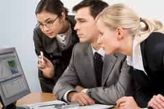 image of smart work group staring at display of computer attentively - stock photo