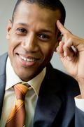 portrait of cheerful businessman smiling and touching his head - stock photo