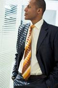 Stock Photo of serious businessman standing and looking through venetian blind in office