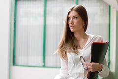 portrait of elegant female with documents and eyeglasses in hand looking aside o - stock photo