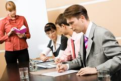 Image of business people working at seminar with their teacher standing near by Stock Photos