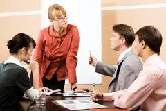 teacher listening explanation of confident businessman at seminar - stock photo