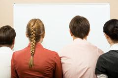 rear view of business team with whiteboard in front of them - stock photo