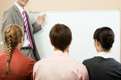 rear view of business partners listening to lecturer and looking at whiteboard - stock photo