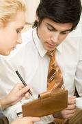 close-up of young man looking at notepad in female's hand - stock photo