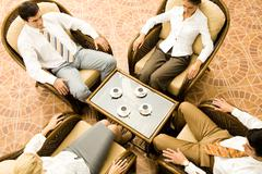 Stock Photo of view from above of sitting business partners during negotiations in office