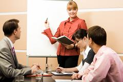photo of smart woman pointing at whiteboard at seminar while business partners l - stock photo