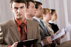 Portrait of confident businessman looking at camera on background of row of his Stock Photos