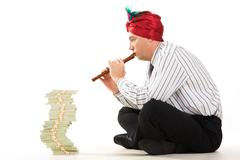 Image of entrepreneur playing the pipe with high stack of dollar bills in front Stock Photos
