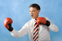 Portrait of screaming boxer wearing red gloves over blue background Stock Photos
